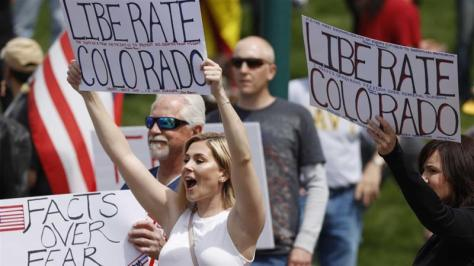 People protest against a state-at-home order issued by Colorado Governor Jared Polis to curb the coronavirus outbreak on April 19, 2020 in Denver, US [AP/David Zalubowski]